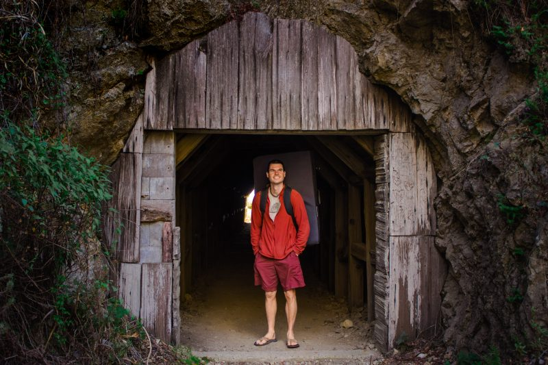 Man standing in the entrance of a tunnel